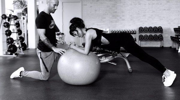 photo of personal trainer Dario Di Lorenzo and his female client performing an exercise on a swiss ball